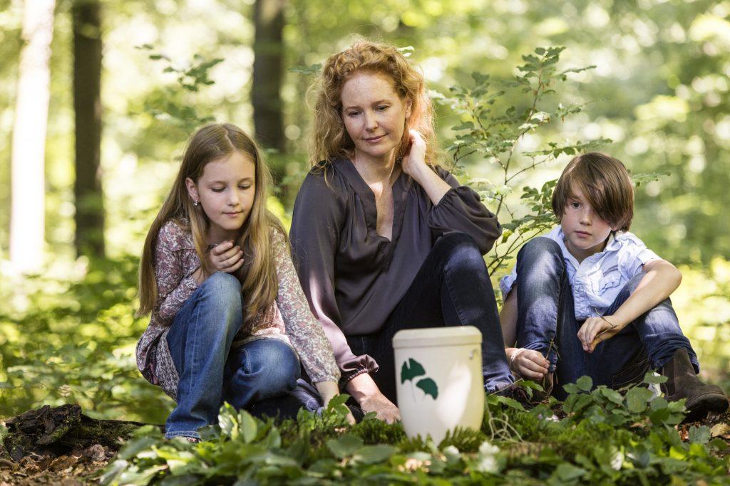 Familie mit Urne bei Friedwaldbeisetzung
